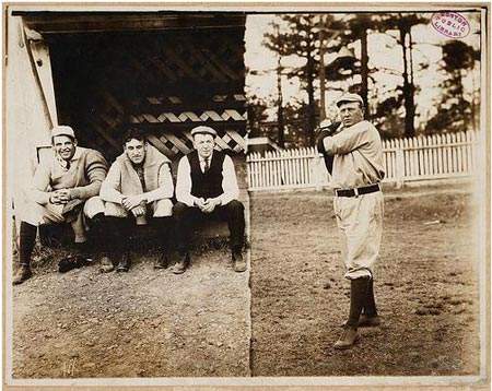 Cy Young posed in pitching motion with three men in dugout watching.