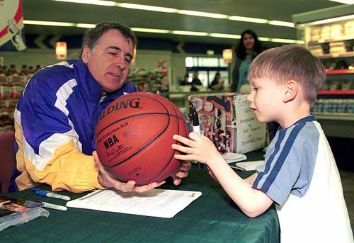 Goodrich (left) autographing a basketball in 2001.